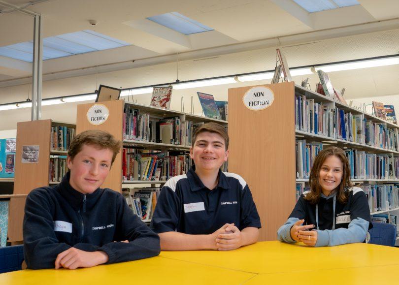 Three students sitting at a school desk